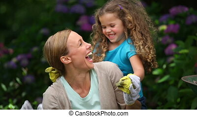 Mother and daughter gardening and playing together