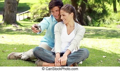 Couple sitting on the grass while photographing themselves