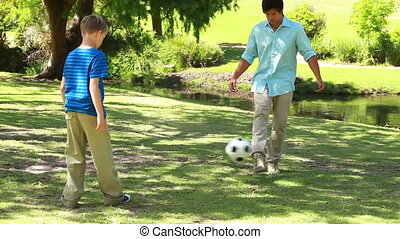 Smiling man playing soccer with his son in a parkland