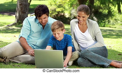 Happy family looking at a laptop while sitting on the grass...