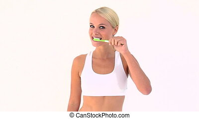 Blonde brushing her teeth against white background