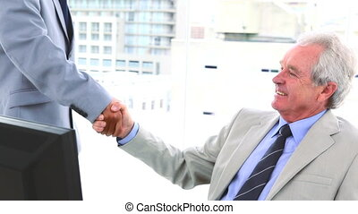 Businessman talking while shaking a hand in his office