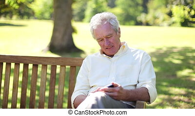 Retired man using a mobile while sitting on a bench