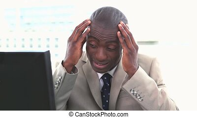 Black man in suit rubbing his head at his desk