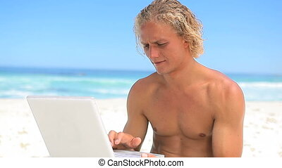 Smiling blonde man holding a laptop