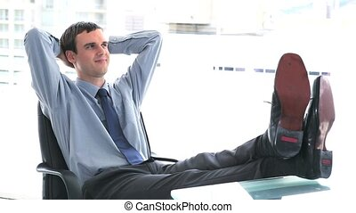 Businessman at ease the feet on his desk in a bright office