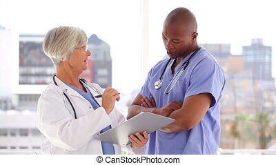Serious mature doctor talking with a nurse in a bright...