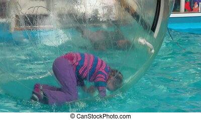 Children in spheres on water