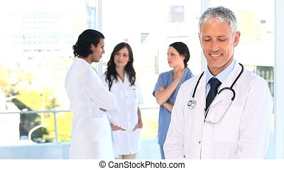 Smiling mature doctor standing upright in front of his team...