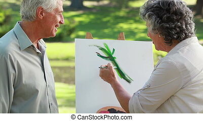 Mature man looking at the canvas of her wife