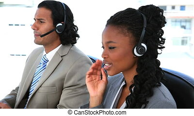 People in suit speaking through headset in a office