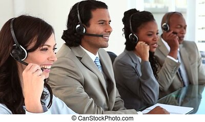 Happy call centre agents wearing headsets in a bright office