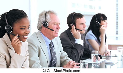 Serious call centre agents talking with headsets in a bright...
