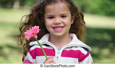 Little girl showing a pink flower while standing in a park