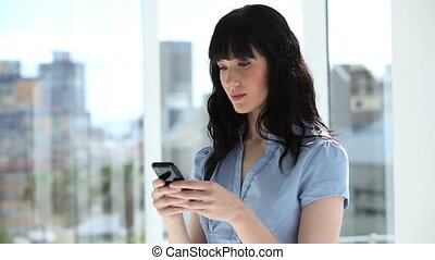 Peaceful businesswoman using her cellphone in a bright room