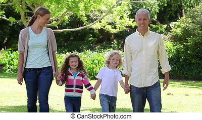 Family walking together in a sunny park