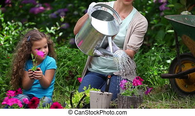 Mother and daughter watering plants in a garden