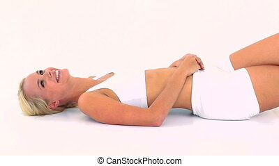 Happy breathless blonde lying on back against white...