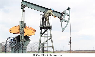 oil worker standing at the pump jack