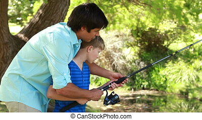 Father and son using a fishing rod together in the...