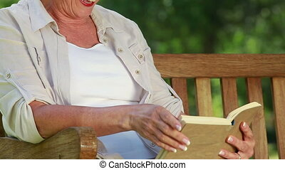 Happy mature woman reading a novel while sitting in a park