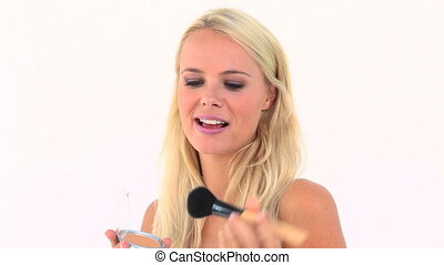 Blonde applying powder on her face against white background