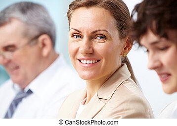 One among the others - Smiling business woman looking...