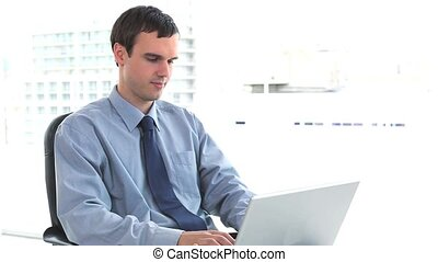 Businessman using a laptop at his office