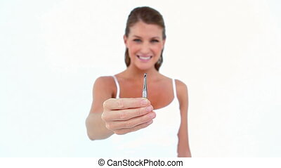 Woman plucking her eyebrows against white background