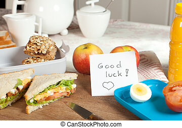 Breakfast table with good luck note - Lunchbox on breakfast...