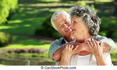 Smiling mature man embracing his wife in the countryside