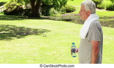 Happy mature man drinking water while standing upright in a...