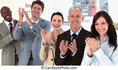 Happy business team applauding together in a bright room