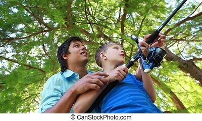 Smiling boy using a fishing rod while being helped by his father in a parkland