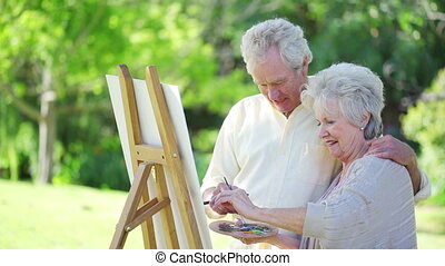 Retired couple painting together outside