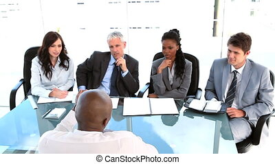Manager talking to his work team in a bright room