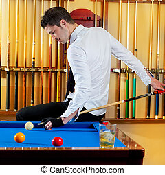 Billiard winner handsome man playing with cue and balls at...
