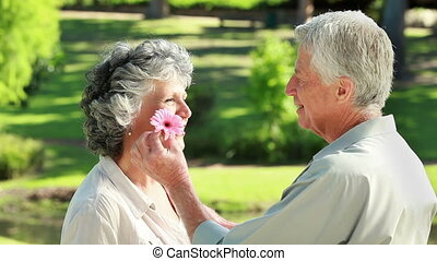Smiling mature man giving a flower to his wife in the...
