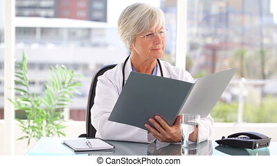 Mature practitioner holding documents in her bright office
