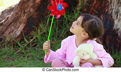 Smiling girl holding a red pinwheel in front of a tree in a...