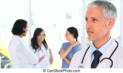 Smiling mature doctor standing in front of his team in a...