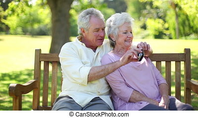 Retired couple taking a picture together in a park