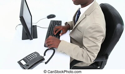 Successful black businessman sitting at his desk against...