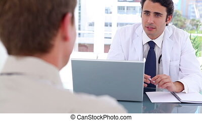 Happy black-haired doctor talking with his patient