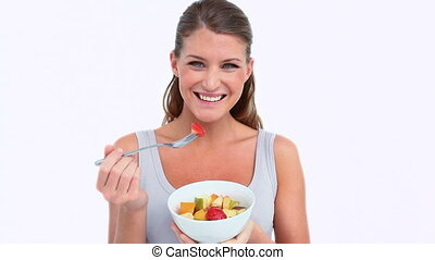 Woman holding a fruits bowl against white background
