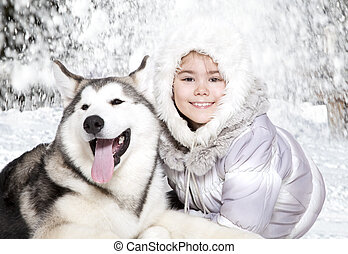 Malamute puppy with a girl - Portrait of a little girl with...