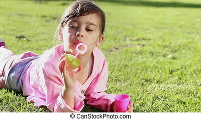 Happy girl making bubbles with a bubble wand in the...