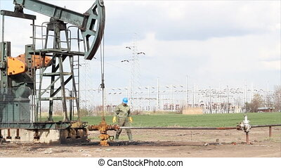 oil worker and pump jack - oil worker check pump jack and...