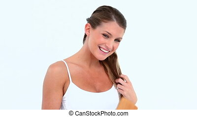 Attractive woman brushing her hair against white background