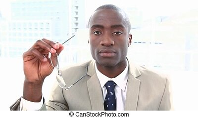 Portrait of a black businessman holding glasses in a office